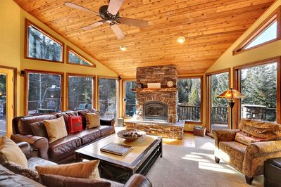 Floor to ceiling windows surround the large stone fireplace in the living room