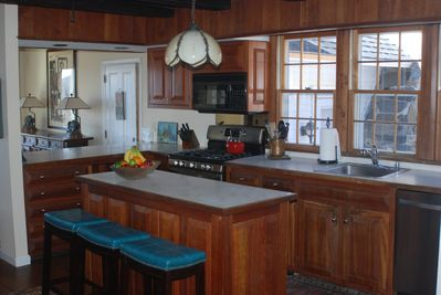 Warm wood-trimmed kitchen with corian countertops