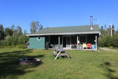 Closer view of the cottage, including the fire pit, picnic tables, and barbecue