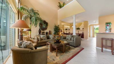Modern open living room with tile flooring, Hawaiian inspired decor, and olive green couches 2