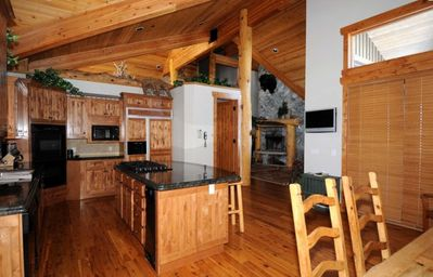 gourmet kitchen with 2 dishwashers, double oven, bar counter, dining room table