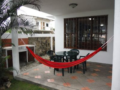 Downstairs front porch with hammocks, BBQ, and seating area.