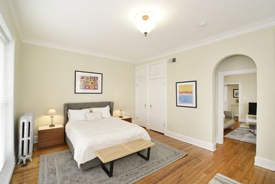 light-filled bedroom with comfortable queen sized bed and plenty of closet space