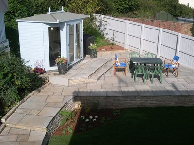 Professionally landscaped rear garden with summer house and garden furniture.