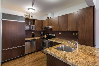 Fully equipped kitchen with granite counter tops, tucked next to the dining room.