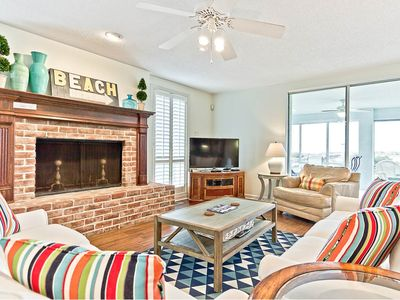 Living area with TV, decorative fireplace and ocean views