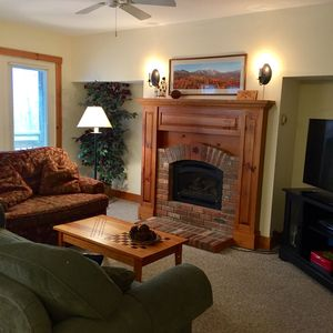 "452A living room with gas fireplace, new 49"" flat screen TV, and view onto deck."