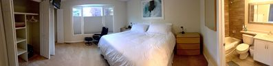 Comfortable master bedroom includes king-sized bed, recliner, television, and full en-suite bathroom.