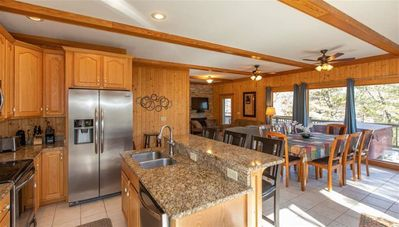 open living room, dining area and kitchen with granite counter tops and island