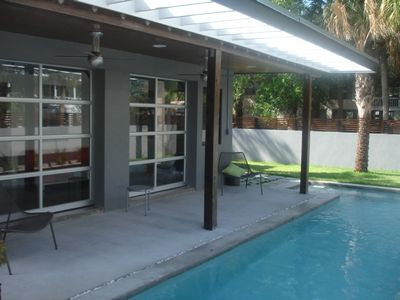 Sunroom with double garage doors on to pool