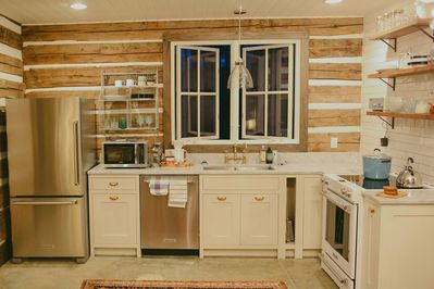 kitchen view with full dishwasher, fridge and full stove
