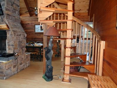 Fireplace opens to living area and dining room. Spiral staircase takes you to the two upstairs bedrooms and bath. Also an upstairs covered deck overlooking the creek is reached from both bedrooms.