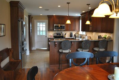 Beautiful kitchen includes bar top dining area and kitchen table.