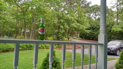 Charming covered front porch looks out to Red Creek Circle