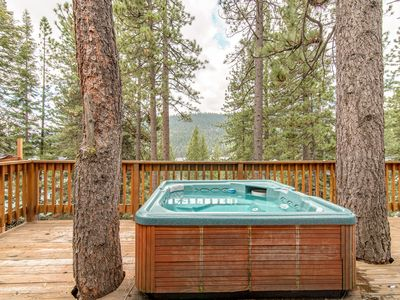 Deck - The private hot tub is nestled between towering pine trees.