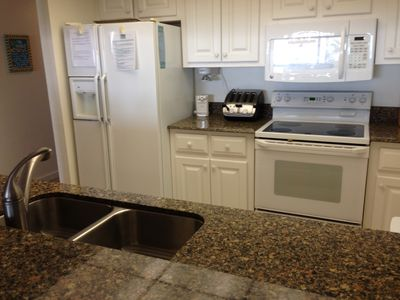 LARGE SIDE BY SIDE REFRIGERATOR AND GLASS TOP ELECTRIC STOVE.