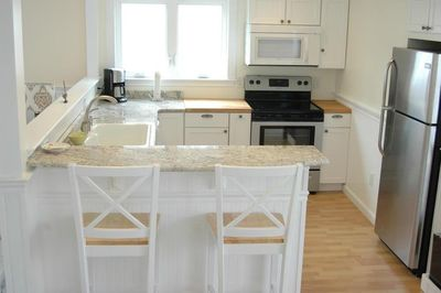 Fully stocked kitchen, stainless appliances and bar seating.
