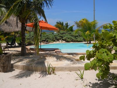 Pool area with shallow end and palapa.
