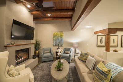 "Living area with 62"" television and cozy gas log fireplace"
