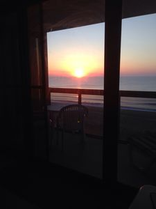 Sunrise from living room couch through floor to ceiling balcony windows/doors.