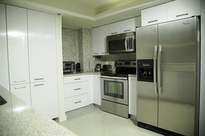 Kitchen contains pots and pans, plenty of cooking utensils and enough dinning sets to use.
