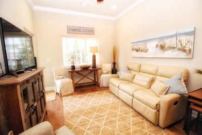 Spacious living area with reclining sofa and additional dining seating.