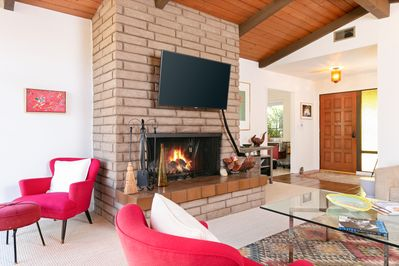 """Living Room - A 50"""" flat-screen TV is mounted above the wood-burning fireplace."""