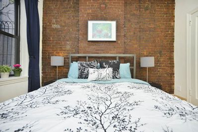 Detail of bed and exposed brick wall