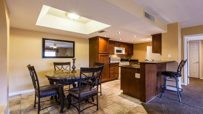 Dining area with kitchen and breakfast bar in background.