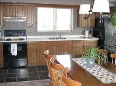upper level kitchen with full size fridge/freezer and electric stove