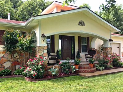 Front of the bungalow in spring. There are roses, hostas, and crape myrtles.
