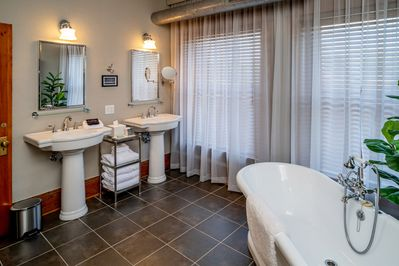The bathroom is very large with two sinks, a shower and a luxurious bathtub.