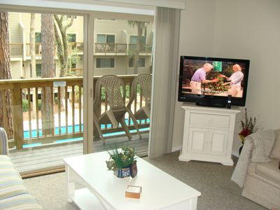 FAMILY ROOM OVERLOOKING POOL WITH COMFORTABLE SEATING, HDTV AND SLEEPER SOFA