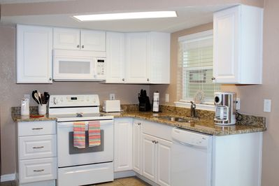 White kitchen with new cabinets and granite