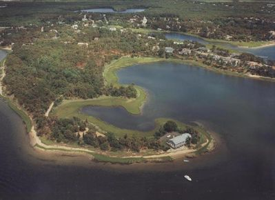 Aerial view of home on private peninsula with private beach.