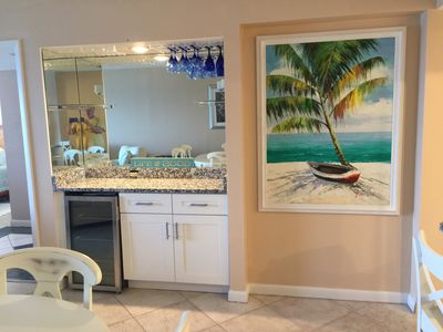 Dry Bar in Dining area with wine cooler and granite counter varitey of glasses