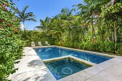 Lush tropical landscaping frames the private salt water pool and hot tub.