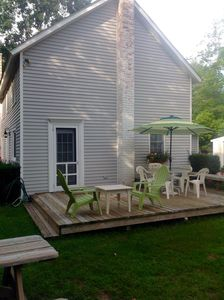 Rear of the cottae with large deck and lots of setting.  Umbrella and bar-b-que.