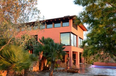 Villa from the garden surrounded by native plants and landscaping