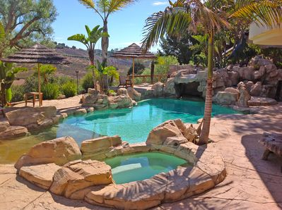 Salt water pool and hot tub with waterfall streaming over 'the grotto.'
