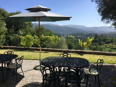 Outdoors dining area with a view over a quiet valley, forest and hills