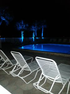 Pool at nighttime with beautiful blue lights around all landscaping & tiki huts
