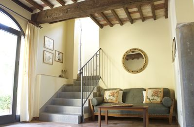 Living room with stone stairs and arched door/windows onto garden.