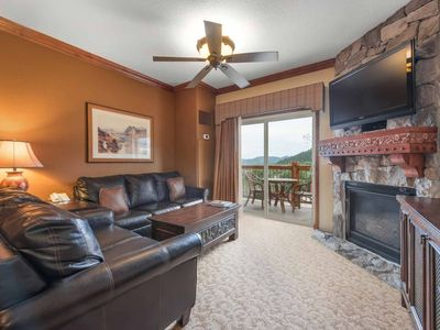 "The living room features two new leather couches, 54"" HDTV, enhanced cable, free Wi-Fi, stone mantle and floor to ceiling stone gas fireplace."