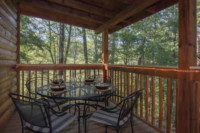 Enjoy the woods from the entry porch.  Rope lights add ambience at night.