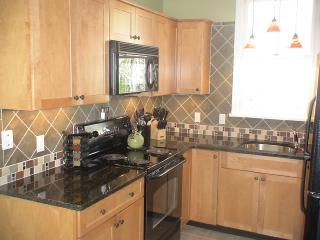 Upscale kitchen with granite counters and tile backsplash