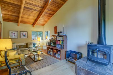 Living room with sectional couch, bookshelf, and wood stove