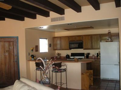 Fully equipped kitchen w/ breakfast bar and iron Southwest high chairs.