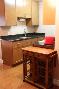 Granite tops, maple cabinets, portable drop leaf breakfast table with stools.