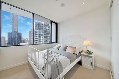 A master bedroom with a queen sized bed & a view of the city